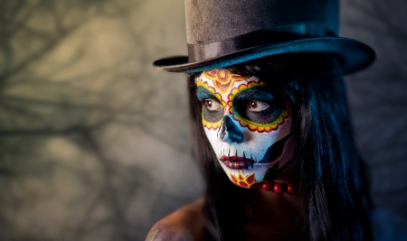 Sugar skull girl in tophat, in the forest  photo