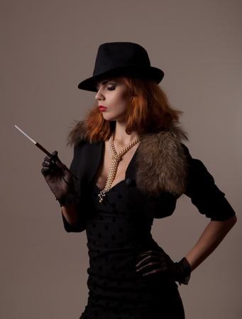 Gangster vrouw in fedora hoed en avondkleding holding mondstuk
