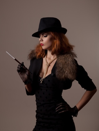 Gangster woman in fedora hat and evening dress holding mouthpiece  Stock Photo