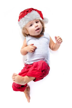 Cute little Santa helper in red pants, high angle view, isolated on white background  photo