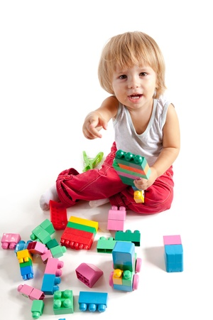 Smiling little boy playing with blocks, isolated on white background  photo