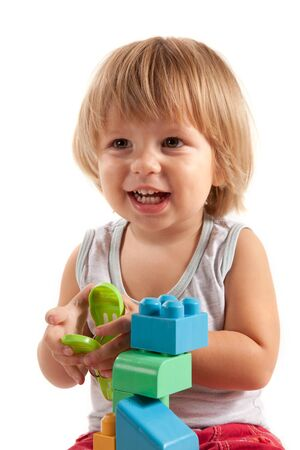 Laughing little boy playing with blocks, isolated on white background  photo