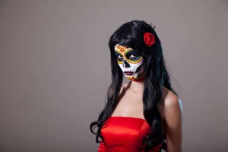 Sugar skull girl in red dress, studio shot  photo