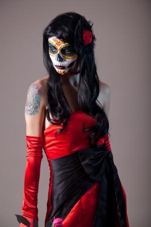 Sugar skull girl in red evening dress, studio shot