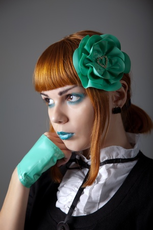Portrait of young redhead woman with blue make-up, latex gloves and hair fascinator  photo