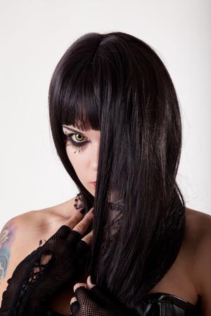 Jonge gotische vrouw met gele ogen en zwart lang haar, studio shot