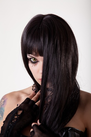 Young gothic woman with yellow eyes and black long hair, studio shot  photo