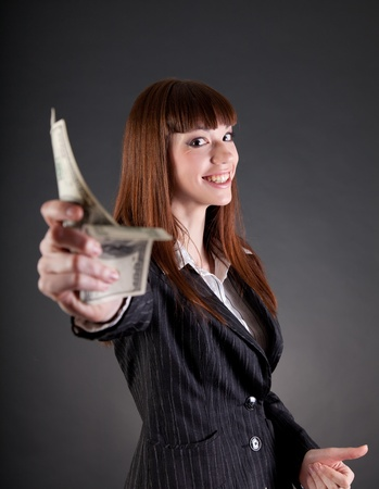 Smiling business woman with dollars offering credit, studio shot  photo