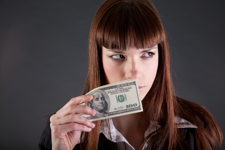 Serious looking businesswoman with dollars, studio shot  photo