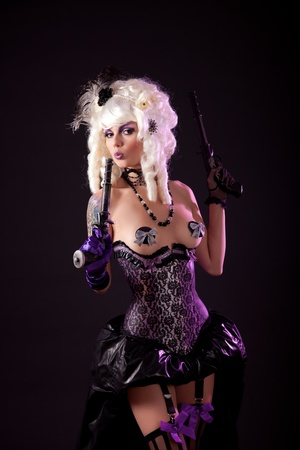 Burlesque girl with guns, studio shot  Stock Photo