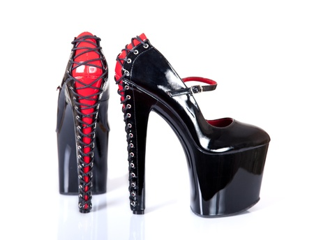 Extremely high heeled fetish shoes with corset lacing, isolated on white background with soft shadow and reflection
