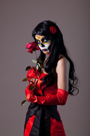 Sugar skull girl with red rose, studio shot  Stock Photo