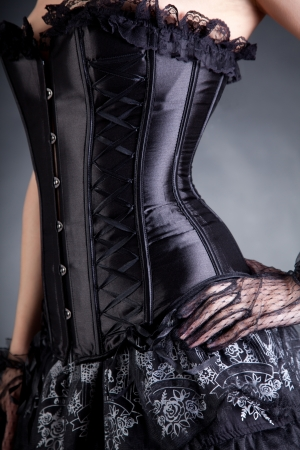 Close-up shot of elegant woman in black corset, studio shot  photo