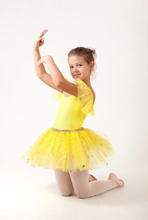 tutu: Cute little ballerina exercising, studio shot on white background