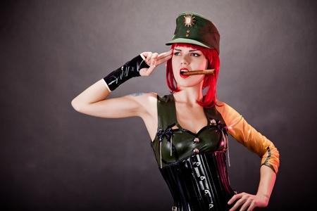 Mladá zrzka žena oblečená ve vojenském stylu latexu a zelenou čepici, studio shot