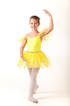 outfit: Smiling little ballerina exercising, studio shot on white background