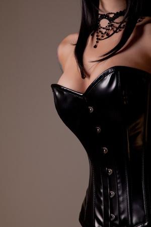 big breast woman: Busty woman in black corset, studio shot on beige background  Stock Photo
