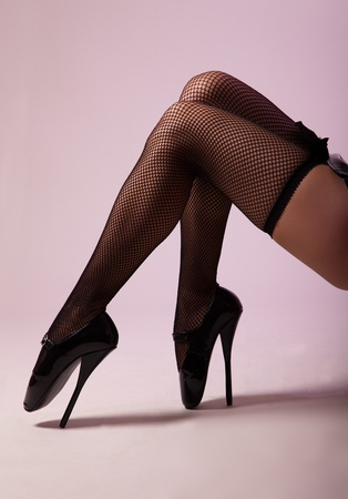 Sexy legs in fishnet stockings and extreme fetish ballet shoes, studio shot