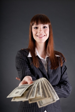 Cheerful business woman with dollars offering credit, studio shot  photo