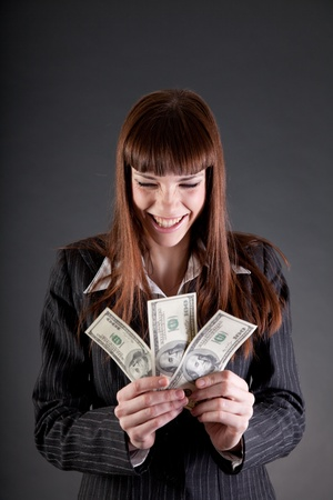 Laughing business woman with dollars, studio shot  photo