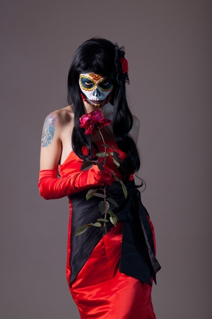 Sugar skull girl with rose, studio shot  Stock Photo