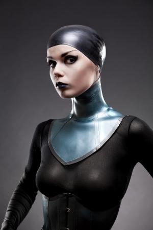Attractive woman in latex neck corset, studio shot on black background