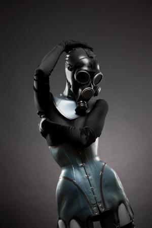 Vrouw in latex corset en gas masker, studio geschoten op zwarte achtergrond