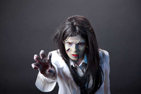 Aggressive zombie girl stretching her hand, professional body-art and contact lenses  photo