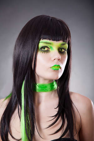 Portrait of attractive woman with green make-up and contact lenses, studio shot  Stock Photo - 13126262