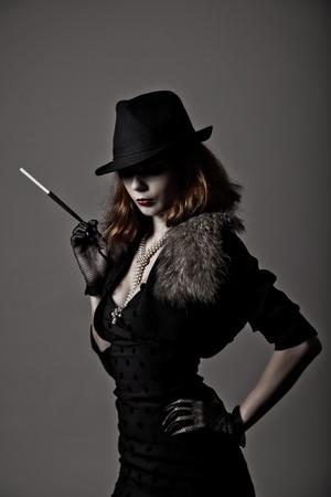 Retro schot van gangster vrouw in fedora hoed en 's avonds jurk bedrijf mondstuk Stockfoto
