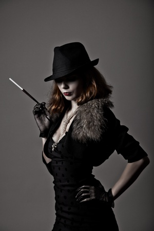 Retro shot of gangster woman in fedora hat and evening dress holding mouthpiece