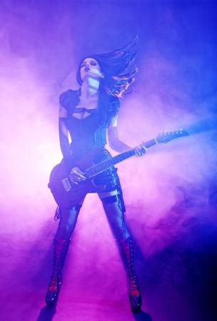 Headbanging sexy woman plays guitar at the concert