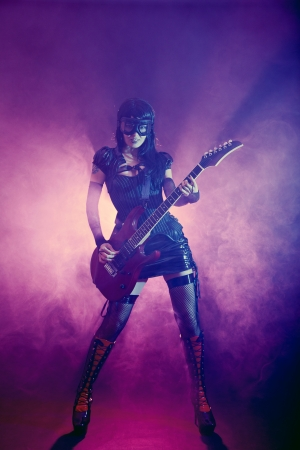 Goth girl in goggles plays guitar on the stage  photo