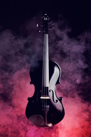 Elegantní černá housle v kouři na červeném a černém pozadí