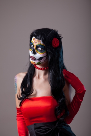 Woman with sugar skull make-up wearing red dress, the Day of the Dead