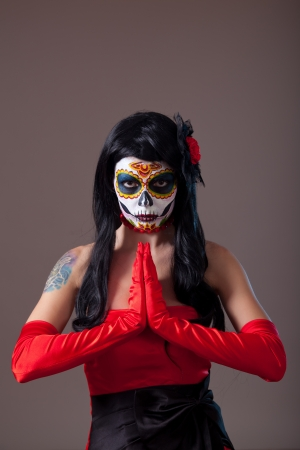 Praying woman with sugar skull make-up, the Day of the Dead
