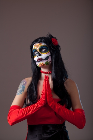 Praying Sugar skull girl in red evening dress and gloves  photo