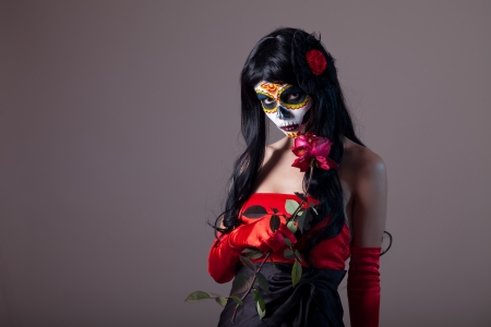 Sugar skull girl holding red rose, Day of the Dead Halloween theme  photo