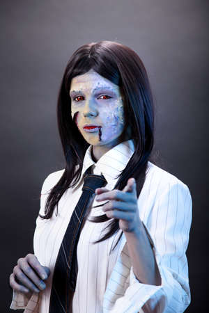 Funny zombie business woman pointing in camera, studio shot  photo