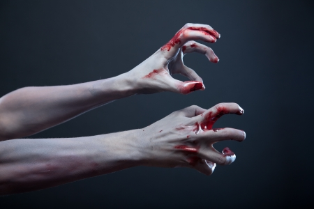 Zombie stretching bloody hands, Halloween theme  photo