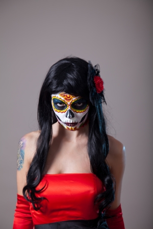 Young woman with sugar skull Halloween make-up wearing red dress, the Day of the Dead  photo