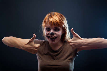 Funny zombie girl showing thumbs up, Halloween holiday  photo