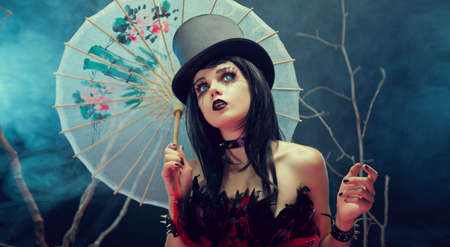 Attractive gothic girl in top hat with Chinese umbrella looking up, studio shot with fog and branches  photo