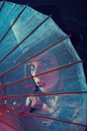 Attractive gothic lady in top hat looking through Chinese umbrella, artistic shot  photo