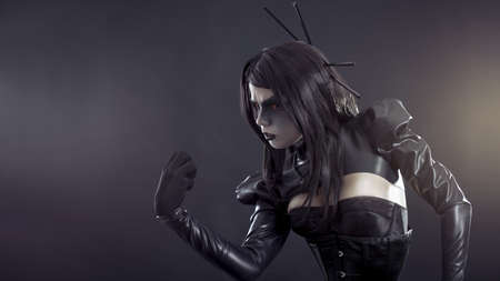 Angry witch with yellow eyes wearing black latex clothes  photo