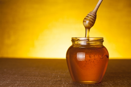 Honey jar with dipper and flowing honey, canvas background  Stock Photo