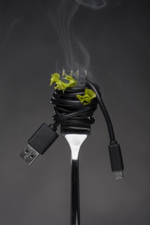 Spaghetti USB cable on fork with salad leaves and smoke, tasty technology concept  photo