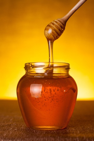 glass jar: Honey jar with dipper and flowing honey, canvas background  Stock Photo