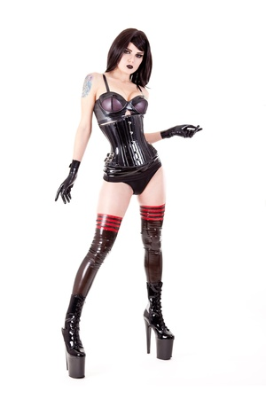 Fetish woman wearing latex outfit and high heels, isolated on white background
