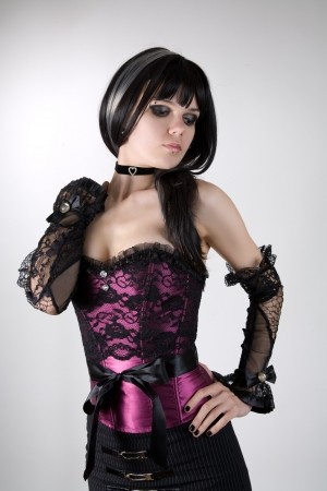 Gothic girl in purple corset and black gloves, studio shot over white background  photo